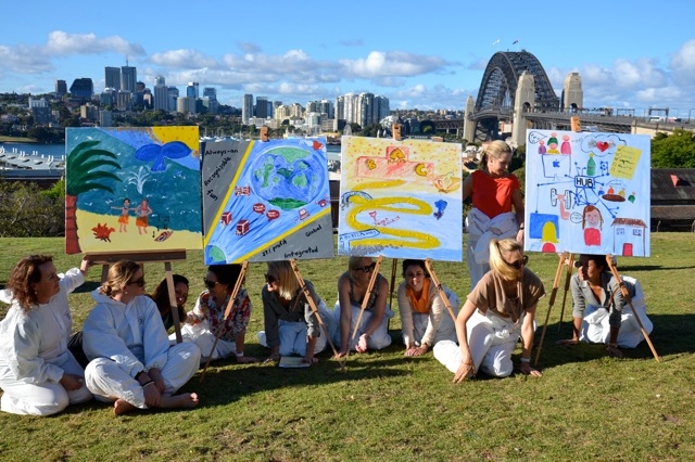 Ladies corporate team display their artworks in front of Sydney Harbour Bridge on easels.