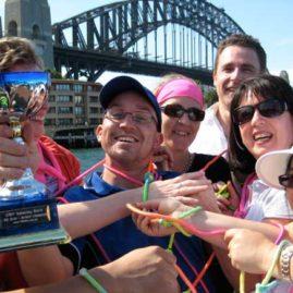Sydney Amazing Race winners hold the Trophy beneath Sydney Harbour Bridge