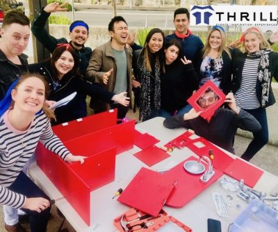 Corporate training teams building red furniture for charities and families in crisis