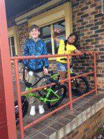 2 kids receive their team building bikes